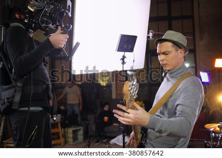 Professional video shooting a musician playing the guitar in the studio - stock photo