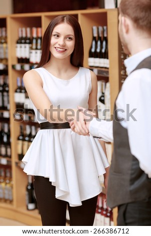 Professional view on wine. Vertical shot of a smiling young woman shaking hands with a sommelier at a liquor store