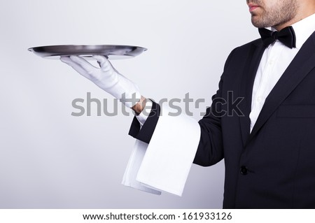 Professional waiter holding empty silver tray over gray background - stock photo