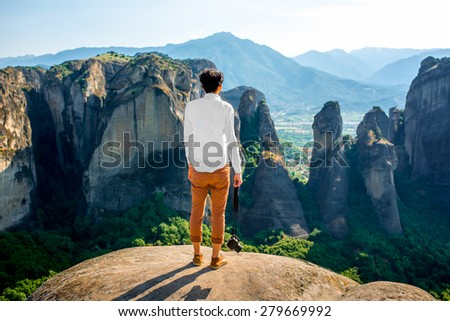 Professional well-dressed photographer standing on the top of mountain on beautiful scenic clif background near Meteora monasteries in Greece. Back view, general plan. - stock photo