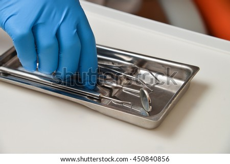 Professional woman dentist doctor working with dental instruments - stock photo