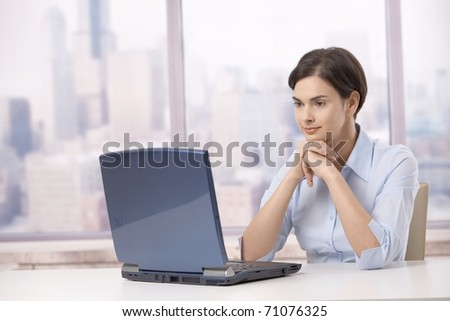 Professional woman sitting at skyscraper office table, looking at laptop computer screen .? - stock photo