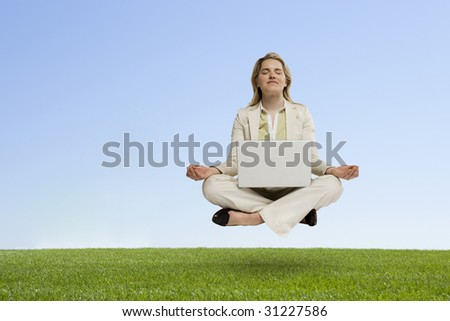 professional woman with laptop seated in zen position hovering over grass - stock photo