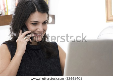 Professional woman working with phone and laptop at workplace