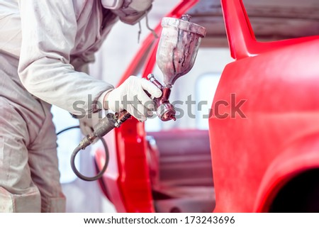 Professional worker spraying red paint on a car body - stock photo