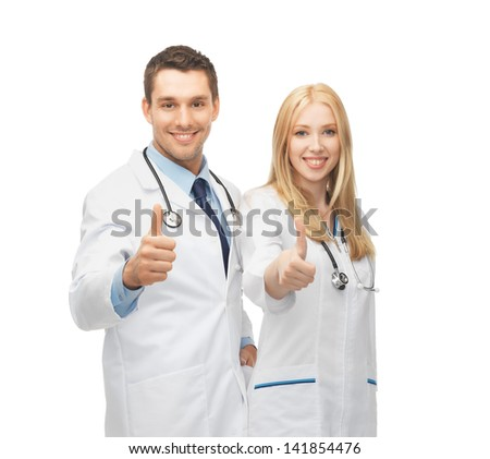 professional young team of two doctors showing thumbs up - stock photo