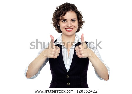 Professional young woman gesturing thumbs up with both her hands, half length portrait.