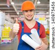 professional young worker with thumbs up sign at shop - stock photo