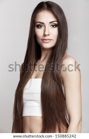 Professionaly  retouched studio HD capture of a beautiful young brunette woman with long hair on grey background - stock photo