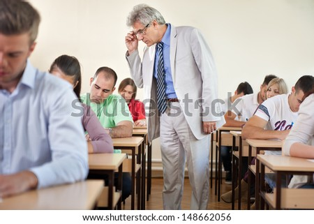 Professor controlling the work of his students in a classroom  - stock photo