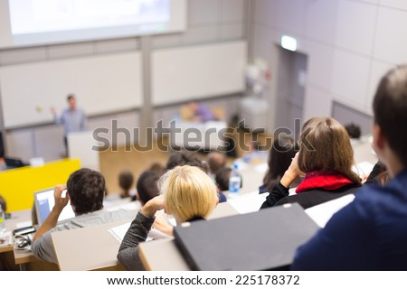 Professor giving presentation in lecture hall at university. Participants listening to lecture and making notes. - stock photo