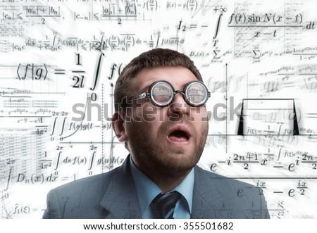 Professor in glasses thinking over math formulas - stock photo