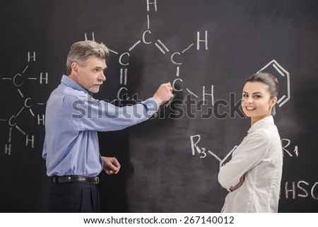 Professor of chemistry writes on the blackboard formula together with his student. - stock photo