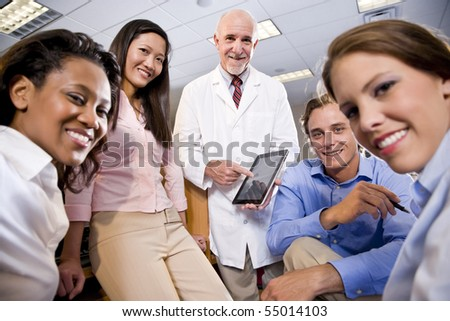 Professor wearing lab coat having discussion with college students - stock photo