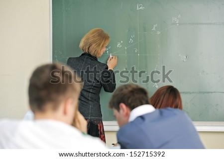 Professor writing on a chalkboard in a classroom - stock photo