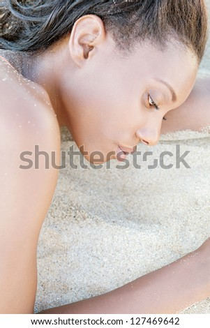 Profile close up beauty portrait of an attractive black woman with perfect skin, laying down on a white sand beach, relaxing. - stock photo
