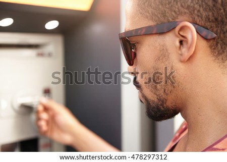 Profile headshot of young handsome serious and concentrated African man in trendy sunglasses trying to check balance on his credit card using automatic teller machine, selective focus on face