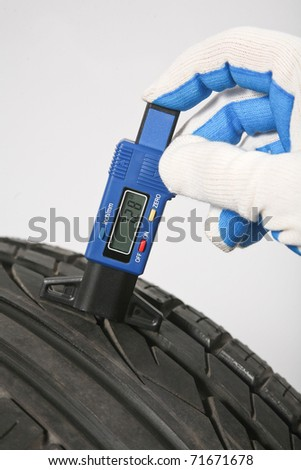 Profile measuring at the car tire with tread depth meter - stock photo