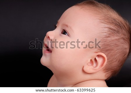 Profile of a baby looking up and smiling. black background - stock photo