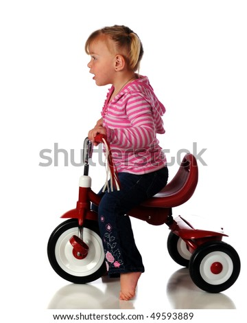Profile of a barefoot two year old riding a little red tricycle.  Isolated on white. - stock photo