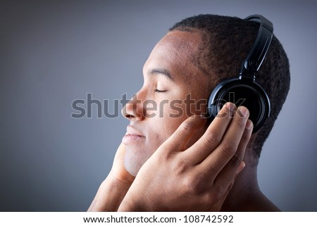 Profile of a beautiful african man listening to music in headphones - stock photo