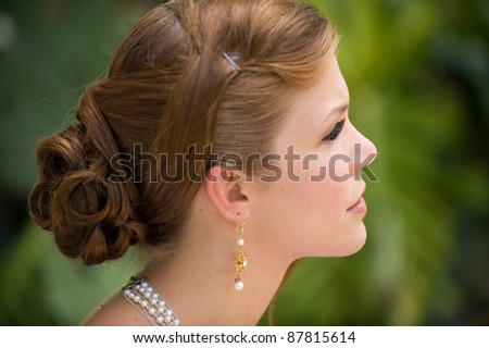 Profile of a beautiful elegant young woman outside - stock photo