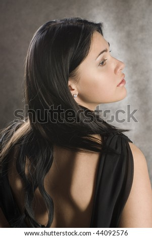 Profile of a beautiful woman in a black dress. - stock photo