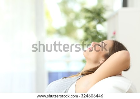 Profile of a beautiful woman relaxing lying on a couch at home - stock photo