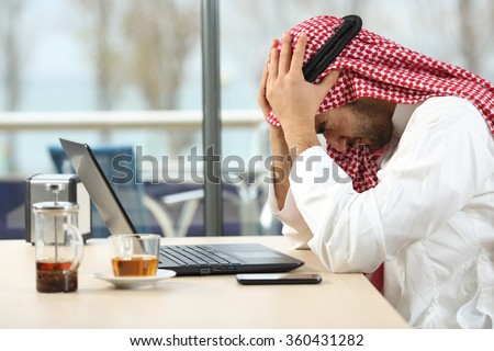 Profile of a desperate and alone arab saudi man with a laptop online in a coffee shop with a window in the background. Bankruptcy concept - stock photo