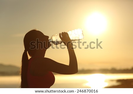 Profile of a fitness woman silhouette drinking water from a bottle at sunset with the sun in the background - stock photo