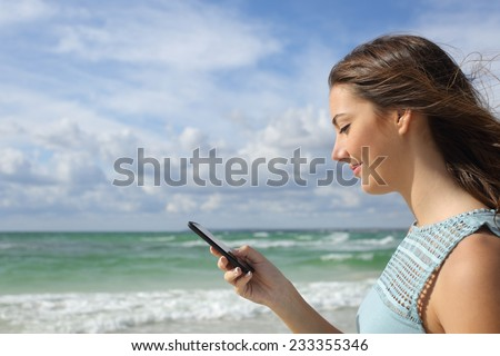 Profile of a girl using a smart phone on the beach with a cloudy sky and horizon in the background - stock photo