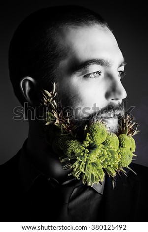 Profile of a handsome man with a beard of green flowers. Men's beauty. Barbershop. - stock photo