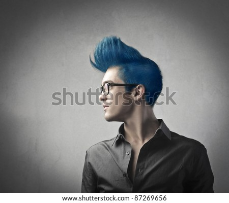 Profile of a handsome man with blue upright hair - stock photo
