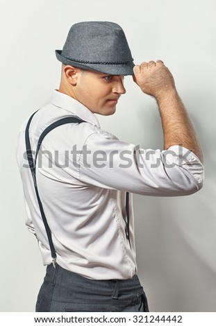 Profile of a handsome young man in hat on white