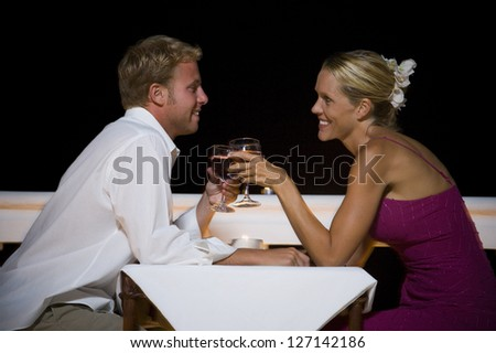 Profile of a man and a woman toasting with wineglasses