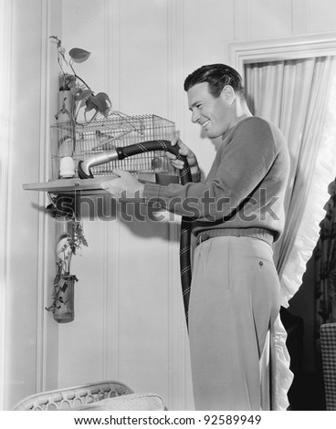 Profile of a man cleaning a cage with a vacuum cleaner - stock photo