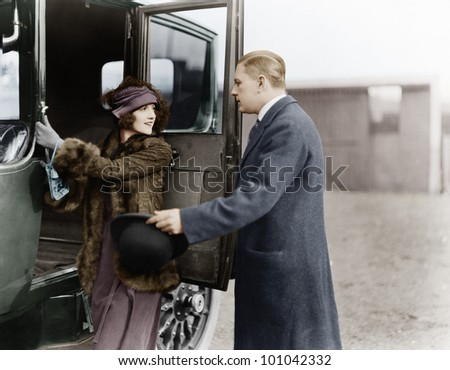 Profile of a man helping a young woman board a car - stock photo