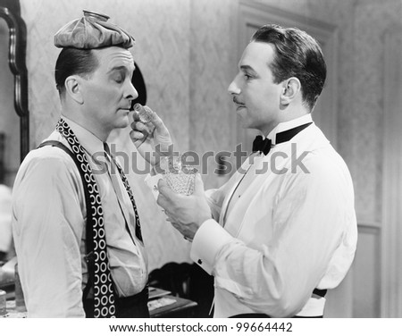 Profile of a man holding a perfume bottle and standing in front of a man with an ice pack on his head - stock photo