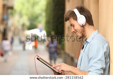 Profile of a man using a tablet with headphones on the street and touching the screen with the finger - stock photo
