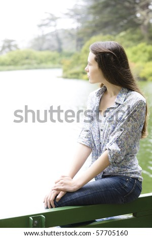 Profile of a Pretty Teen Girl Sitting on a Bench in a Park