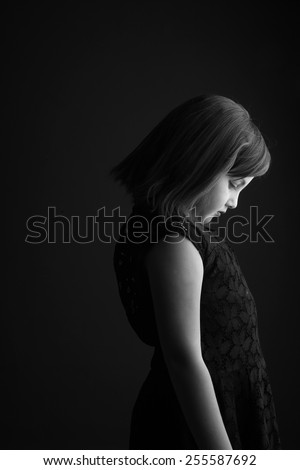 Profile of a small girl looking down, monochrome - stock photo