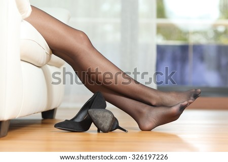 Profile of a tired woman legs with black nylons resting on couch at home after work - stock photo