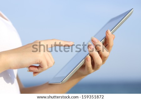 Profile of a woman hands holding and browsing a digital tablet on the beach with the sky in the background - stock photo