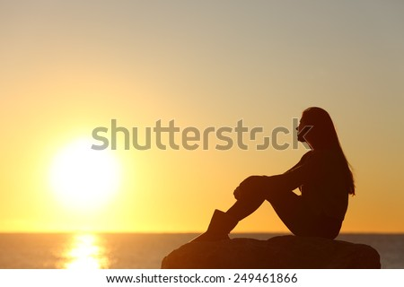 Profile of a woman silhouette watching sun on the beach at sunset - stock photo