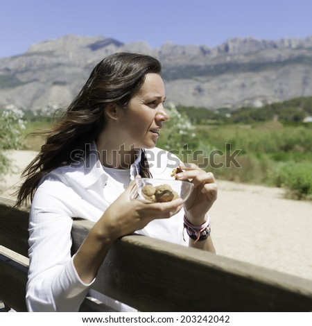 profile of a woman sitting on a bench eating nuts in the park  - stock photo