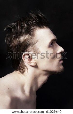 Profile of a young handsome man on black background - stock photo