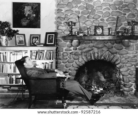 Profile of a young man resting in an arm chair near a fireplace - stock photo