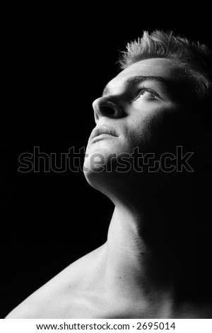 Profile of a young man staring dreamfully upwards in black and white - stock photo