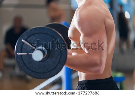 Profile of a young man working out in the gym - stock photo
