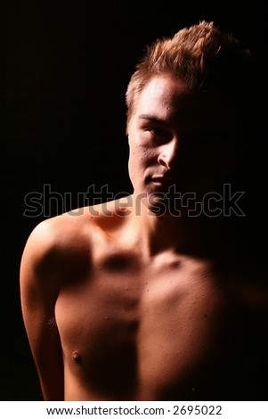 Profile of a young muscular man staring into the camera in color - stock photo